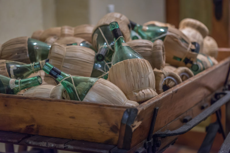 picture of many vintage, wine bottles on the cart