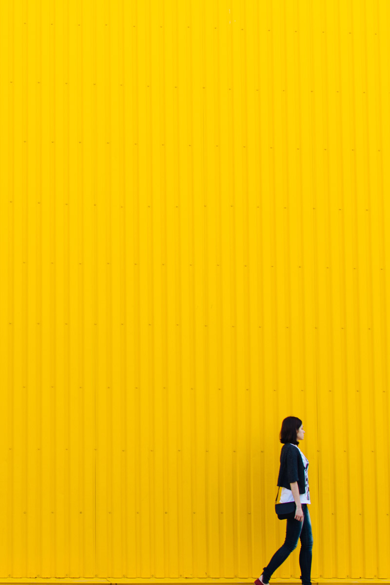 Woman walking in front of yellow background