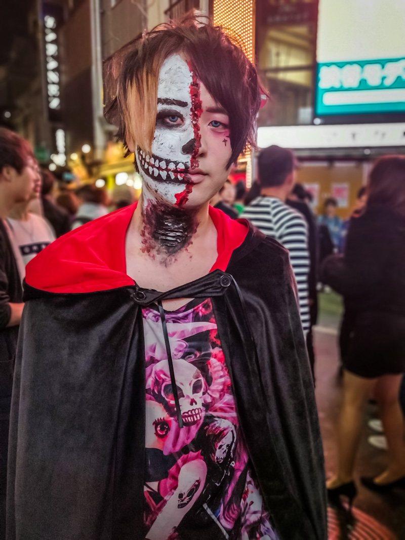 Halloween makeup of half a zombie, half a man.