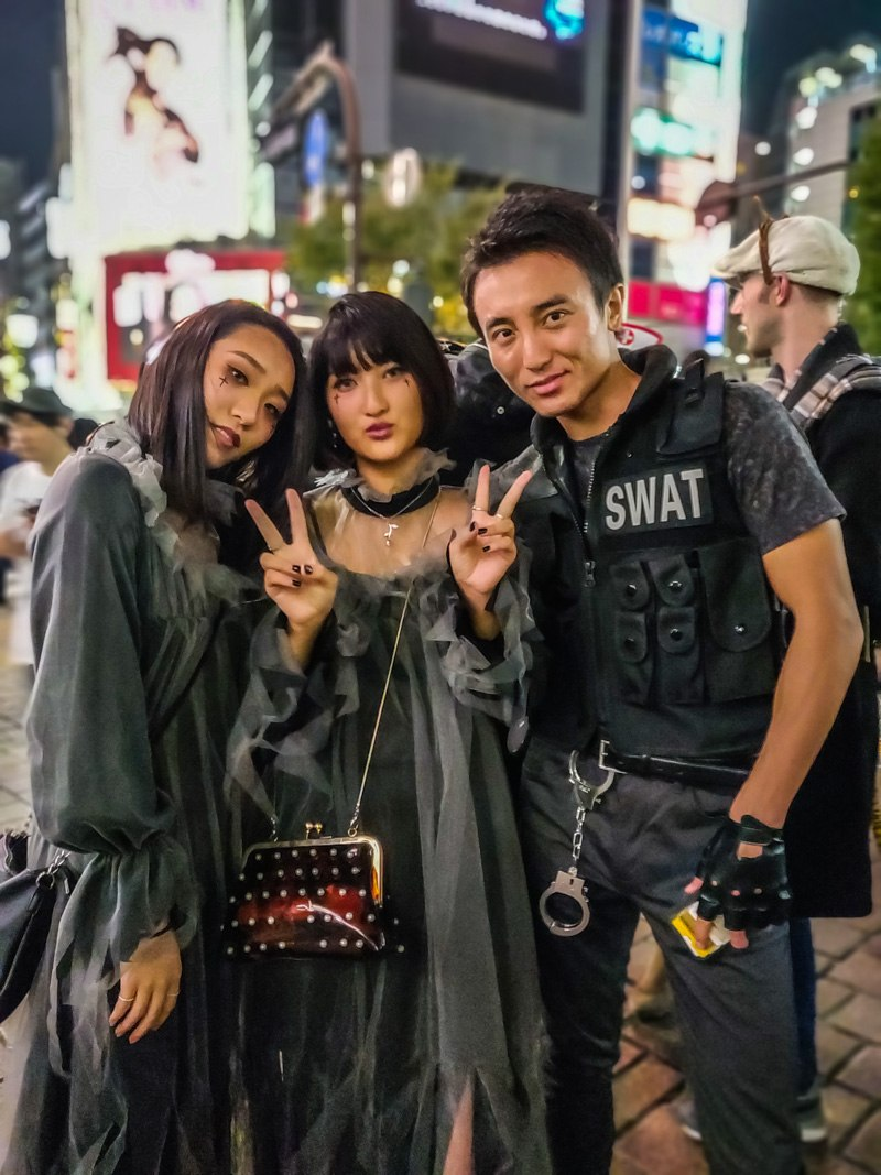 SWAT team member with two women during Halloween in Shibuya.
