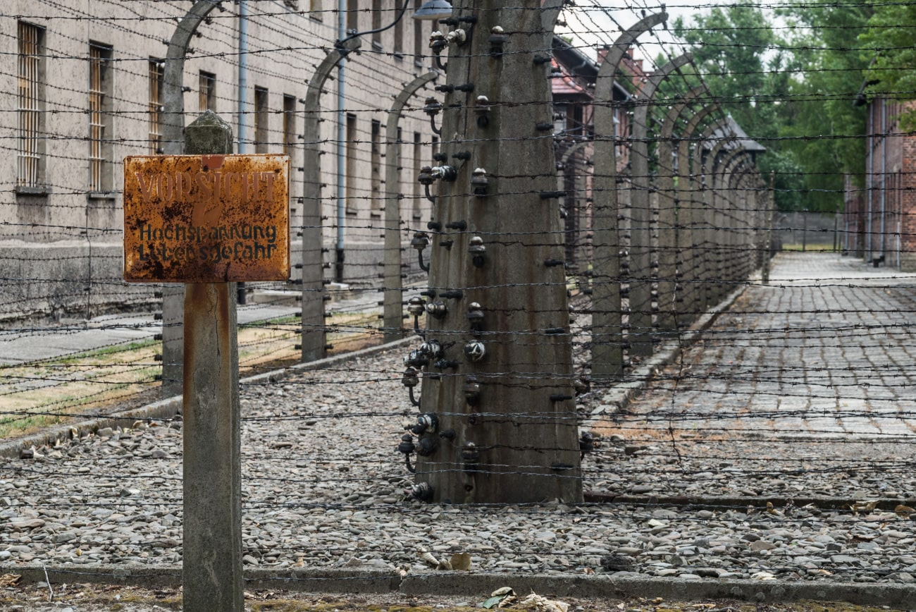 High Voltage Electric Fence with Rustic German Warning Sign in Auschwitz