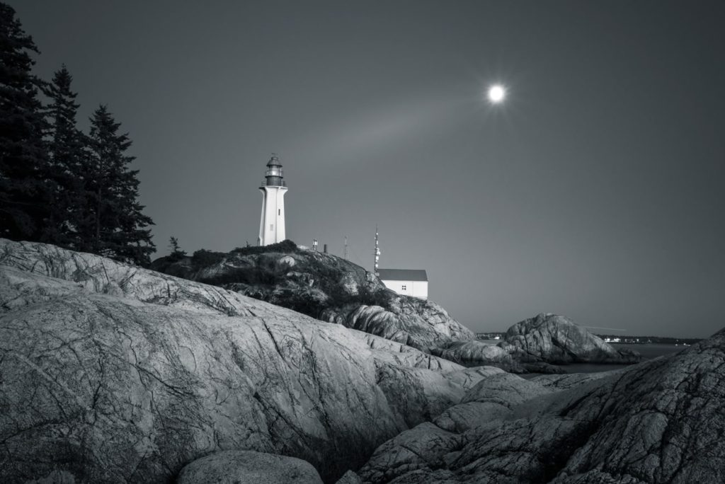 Lighthouse in Black and White in West Vancouver, Canada with rising moon landscape.