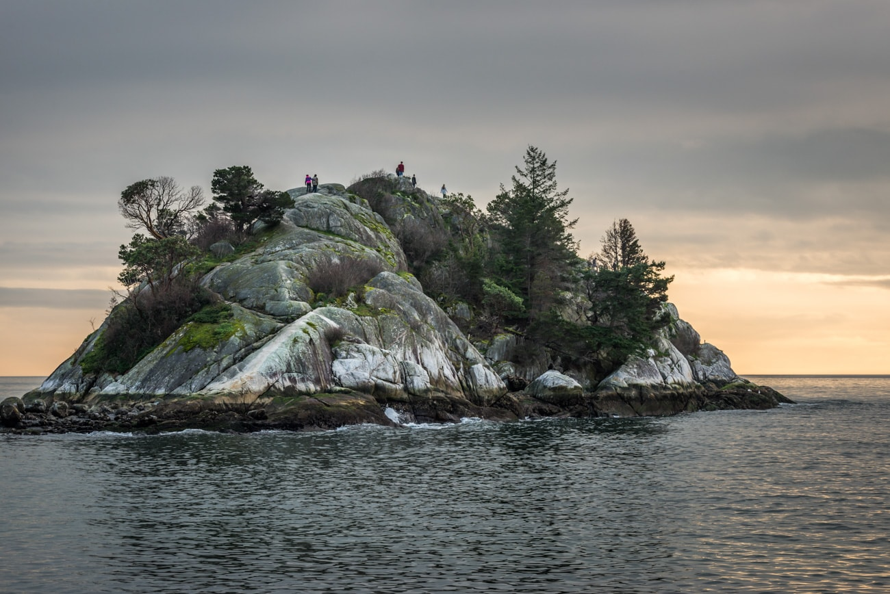 Big rock and people in Whytecliff Park at Sunset.