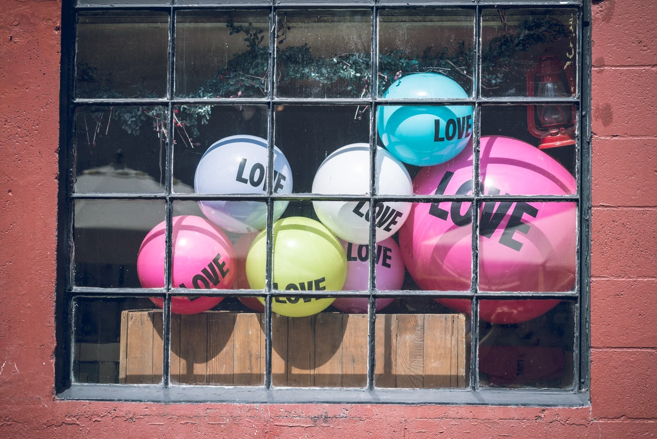 Colorful Love balloons behind a window with iron bars.
